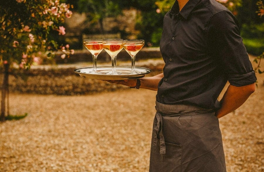 A waiter stands and holds a tray with champagne filled glasses