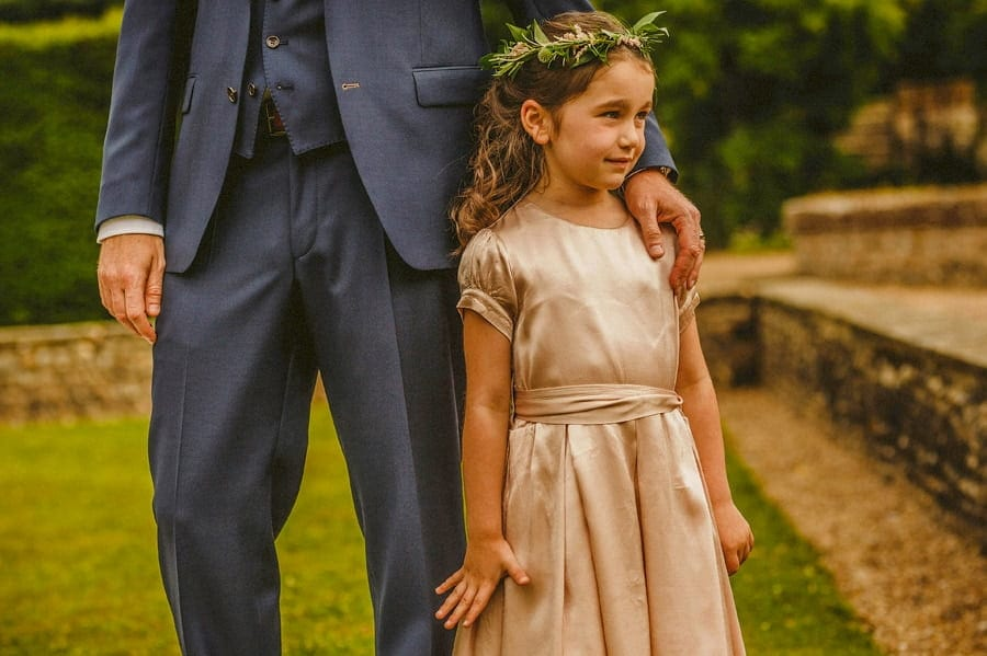 A flower girl stands next to the groom on the front lawn at Voewood House in Norfolk