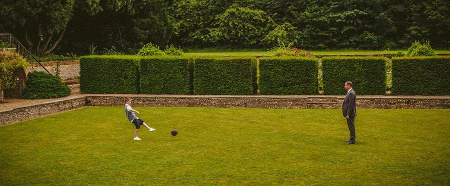 A boy kicks a football towards his father on the lawn at Voewood