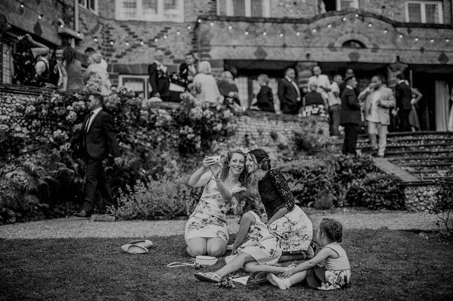 Wedding guests taking photographs of themselves on the front lawn at Voewood House