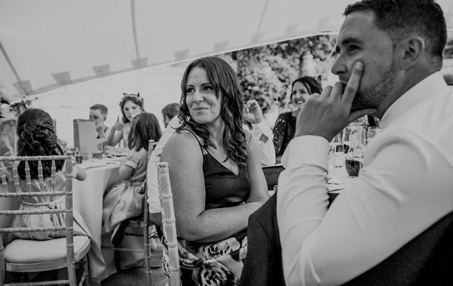A wedding guest sat at the wedding table in the marquee smiles as she listens to a speech