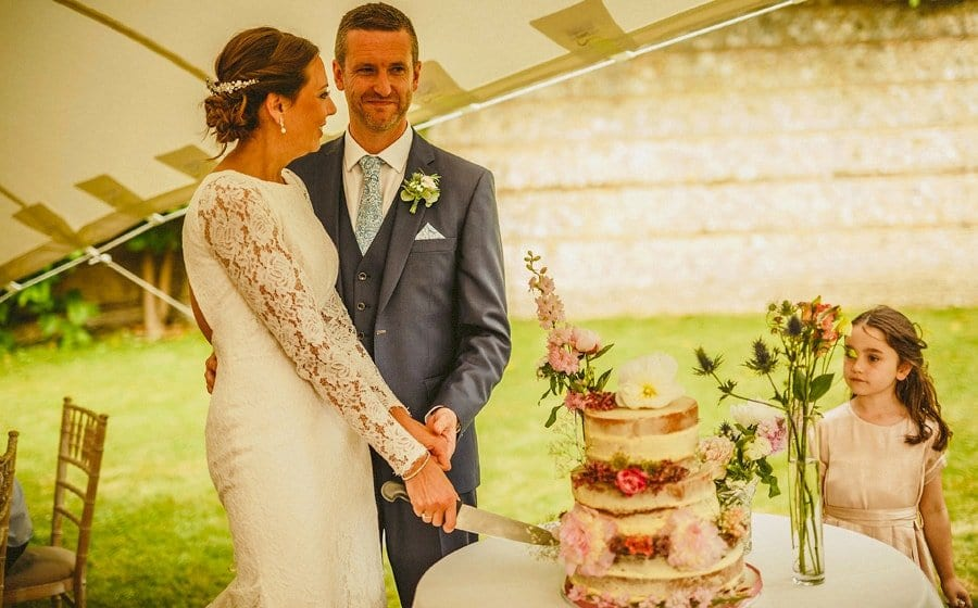 The bride and groom cut the cake in the marquee at Voewood