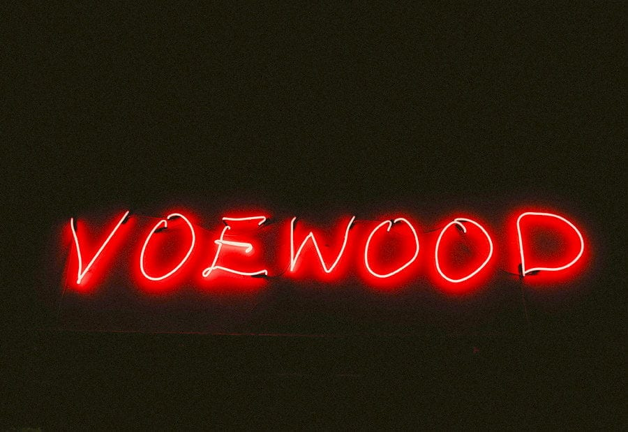 A neon sign which reads VOEWOOD