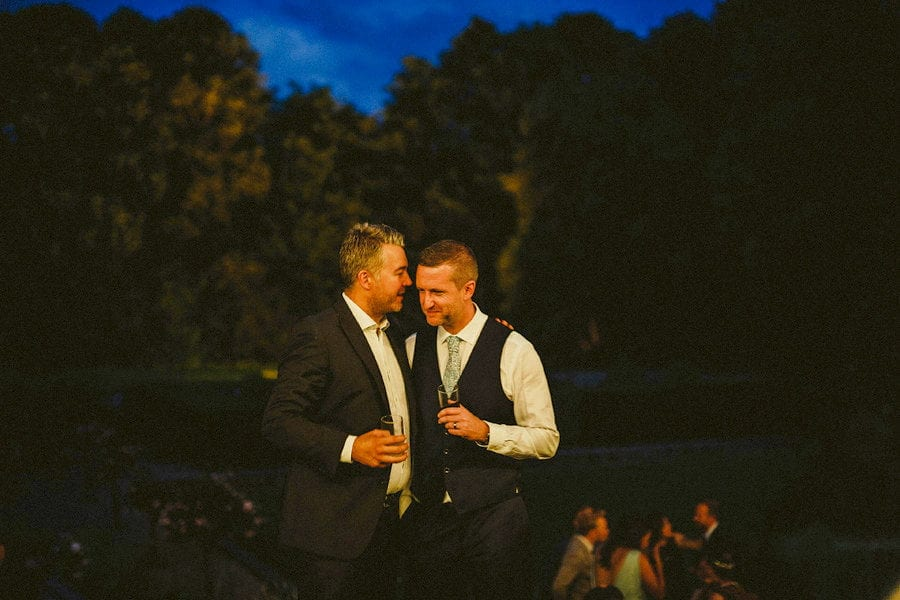 The groom chats with a friend at the back of Voewood House in Norfolk