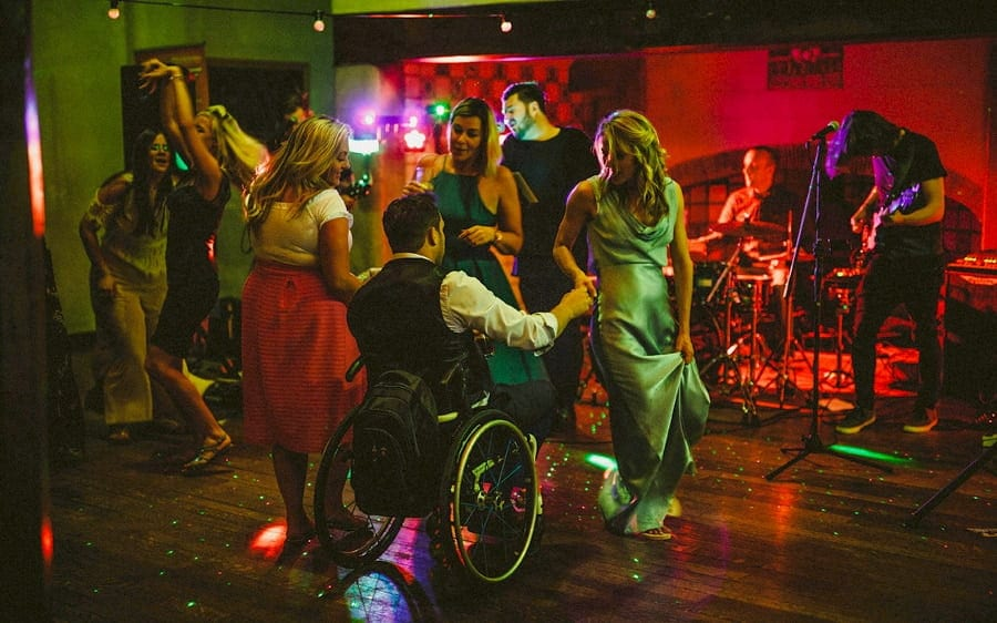 A man in a whell chair dances with a bridesmaid on the dancefloor at Voewood