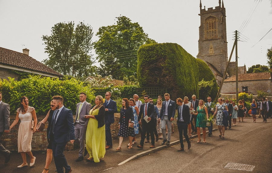 Wedding guests leaving the church and walking down the street