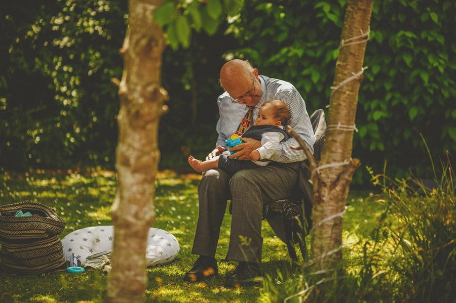 A man holds his great grandson in the garden