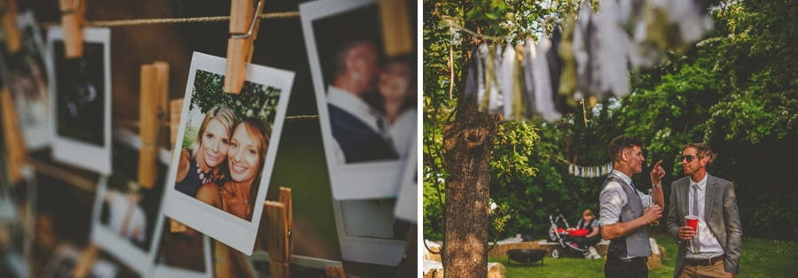 A polaroid photograph hangs on a piece of string with a page attached to it and wedding guests chat in the garden