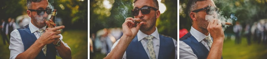 The groom lights up his cigar in the back garden of his parents house
