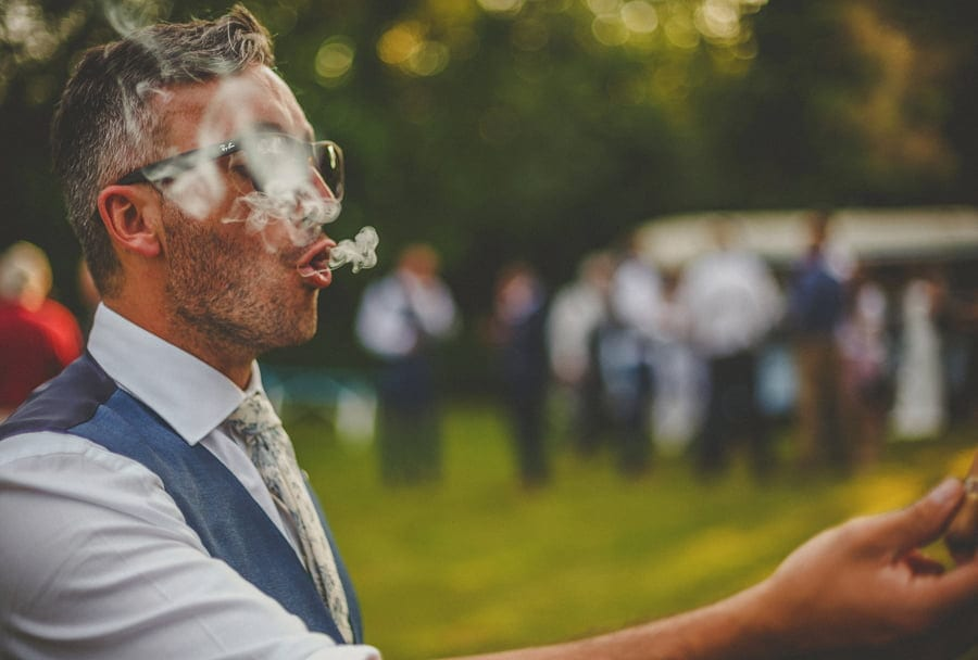 The groom exhales smoke from a cigar