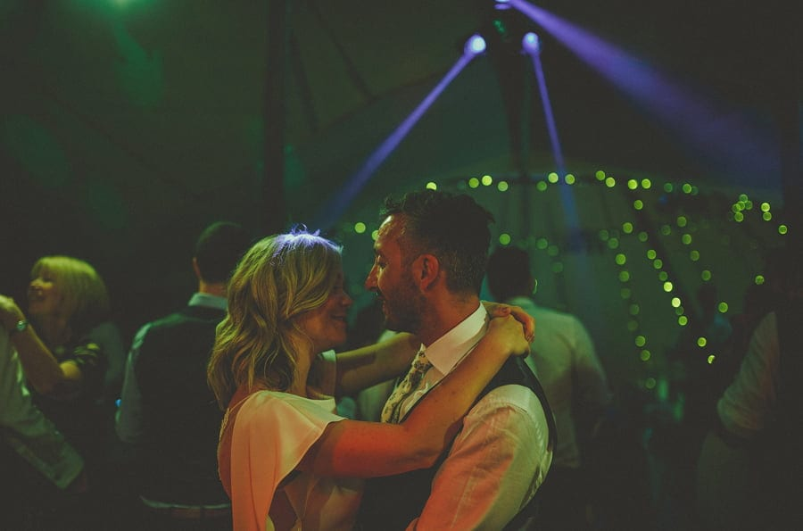The bride and groom look and embrace each other on the dancefloor of the tipi