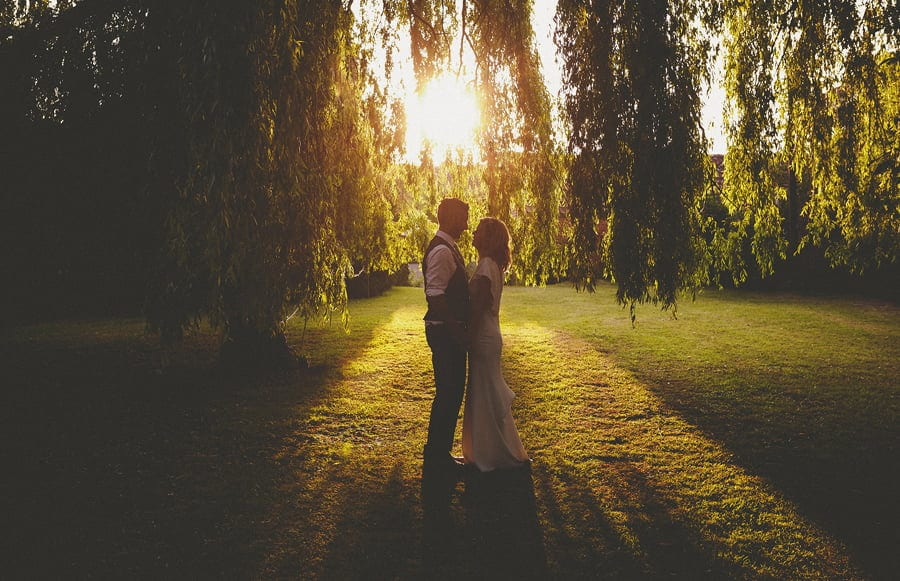 The bride and groom embrace each other under a weeping willow tree as the sun sets