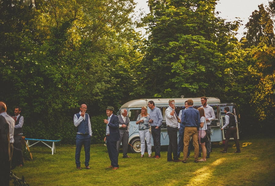 Wedding guests congregate on the lawn next to the cocktail van