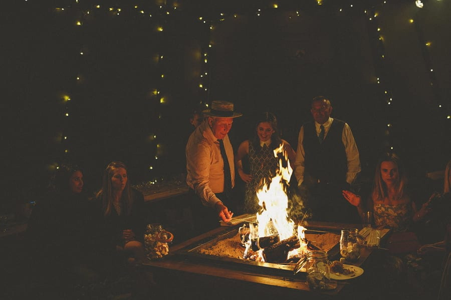 Wedding guests gather around the fire pit to toast marshmallows in the tipi