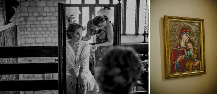 The bride looks in the mirror as the hair stylist pins the back of the brides hair in the old barn