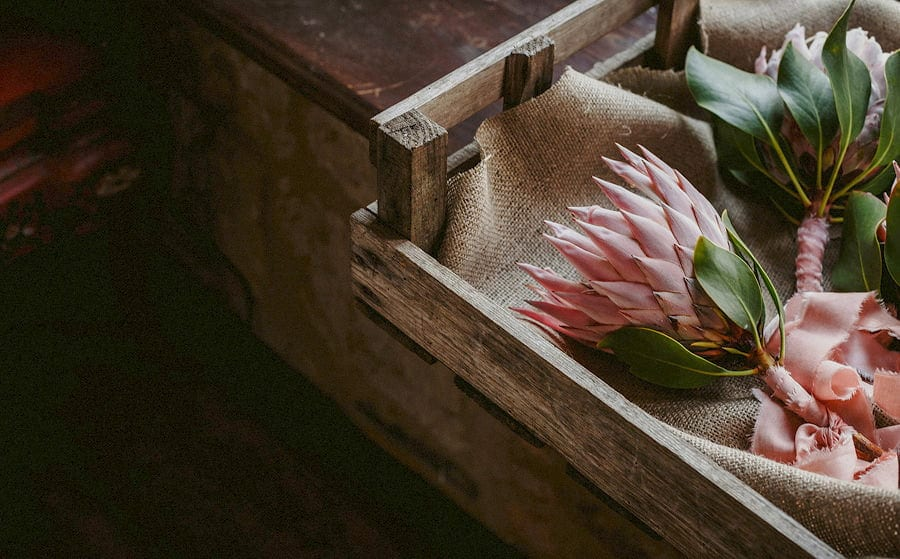 The brides pink wedding flowers in a wooden box rest on cloth