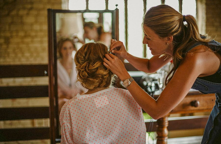 The hair stylist pins the right side of the brides hair as the bride looks in the mirror