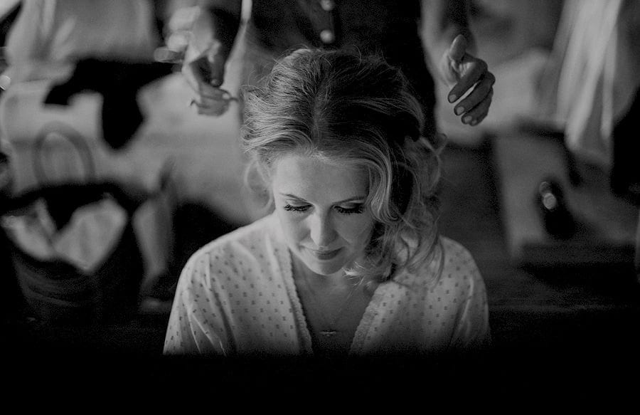 The bride looks down as the hair stylist shapes the brides hair in the old barn at Childerley