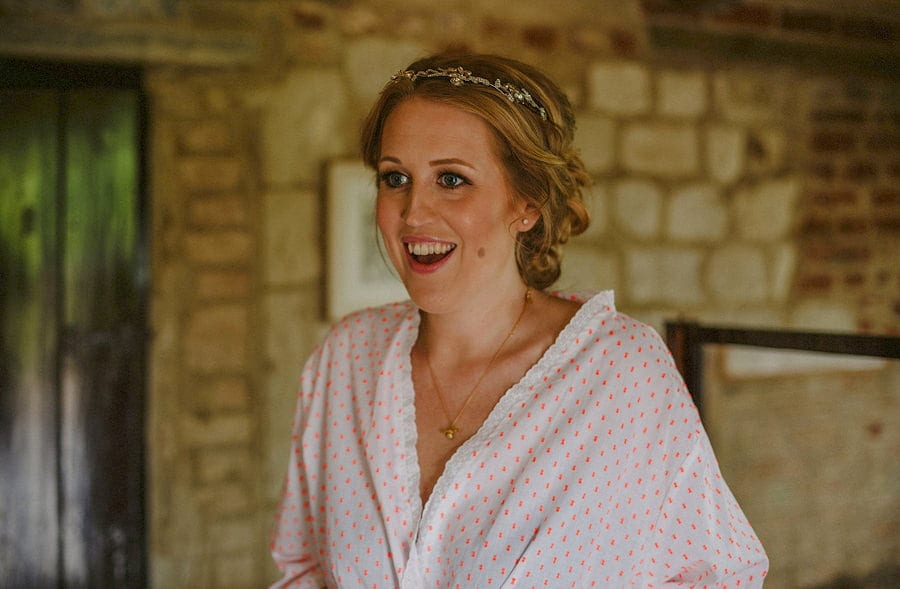 The bride smiles as she listens to her bridesmaid in the old barn