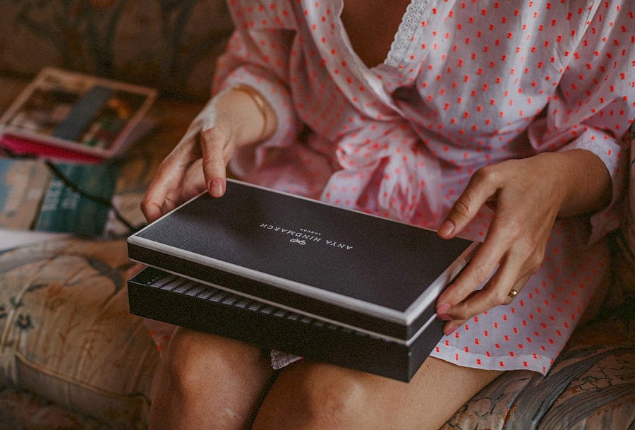 The bride opens a black box which is resting on her lap in the old barn