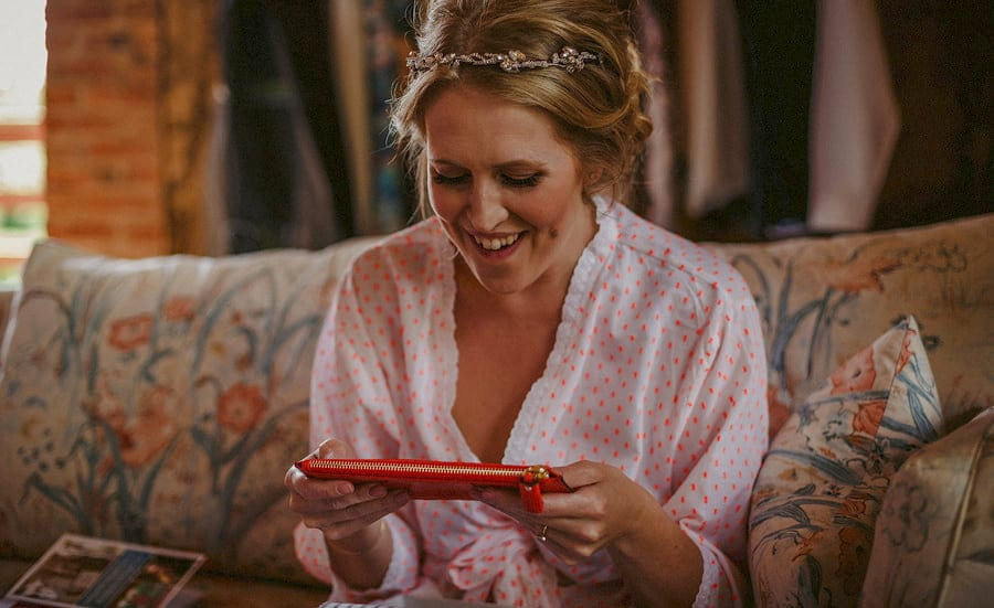 The bride holds a red purse in both hands and smiles in the old barn
