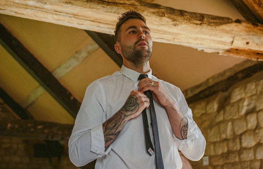 The bride's brother fastens his tie and looks in the mirror in the old barn