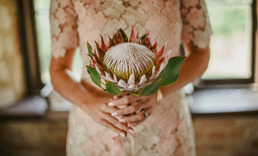 A bridesmaid holds a large flower in both hands