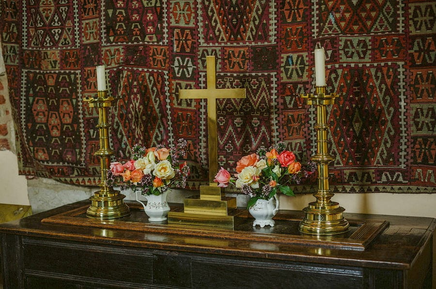 A gold cross and candles rest on a large wooden cabinet in the chapel at Childerley