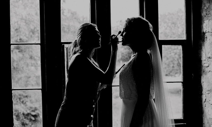 The makeup artist brushes foundation onto the bride's face next to a large window in the old barn at Childerley