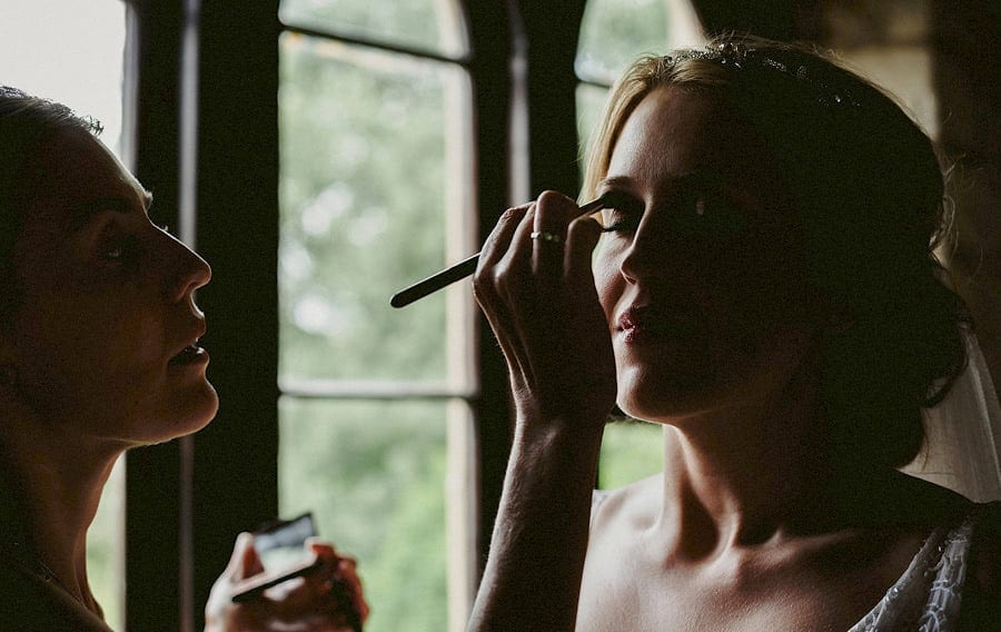 The makeup artist brushes mascara onto the brides right eyelid in the old barn at Childerley