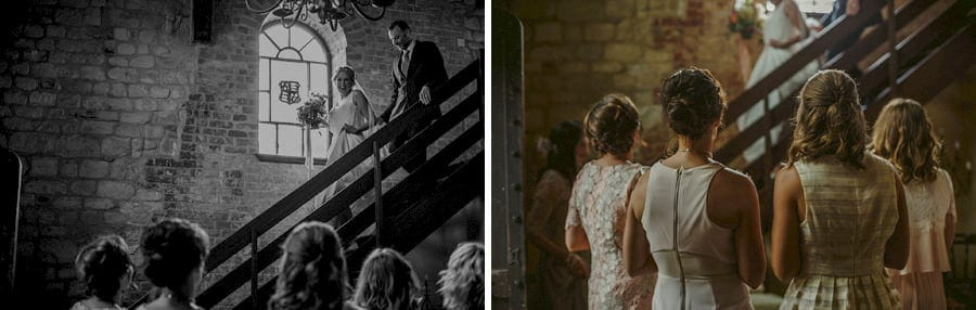 The bride walks down the wooden staircase in the old barn as the bridesmaids stand and watch