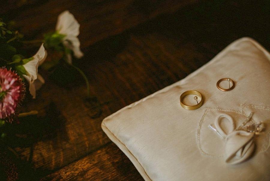 The wedding rings lay on a cream cushion