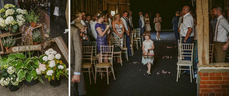 A flower girl walks down the aisle at the old barn in Chelderley and drops petals from a wicker basket