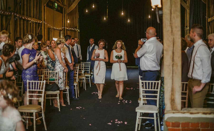 Two bridesmaids walk side by side down the aisle in the old barn at Childerley Estate in Cambridgeshire