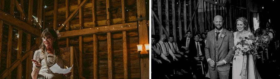 The bride and groom stand next to each other as they listen to a reading by the bride's mother in the old barn during the wedding ceremony