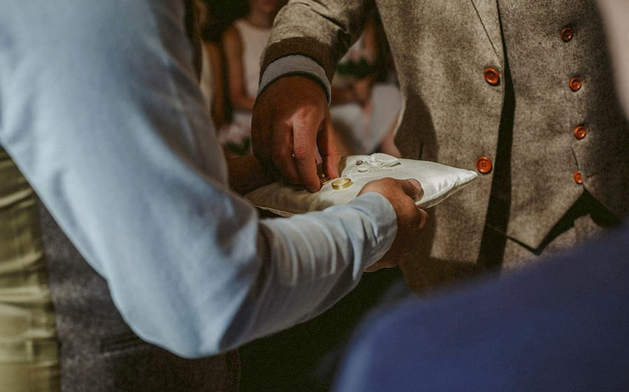 The groom takes a wedding ring from the cushion during the wedding ceremony