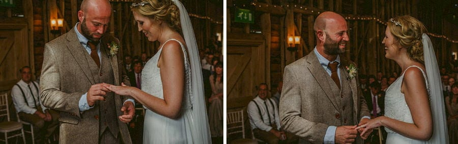 The groom places a ring on the finger of the bride during the wedding ceremony in the old barn