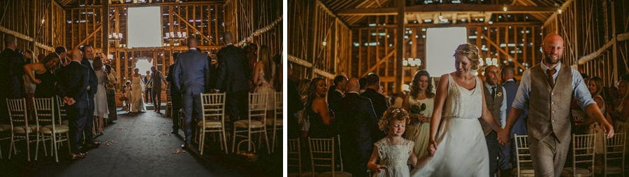 The bride and groom walk hand in hand out of the old barn