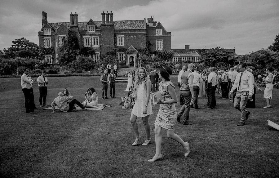 Wedding guests smile at each other as they walk across the back lawn at Childerley Estate in Cambridgeshire