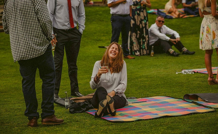 A lady lies on a multi coloured blanket holding a glass of wine and laughs with friends