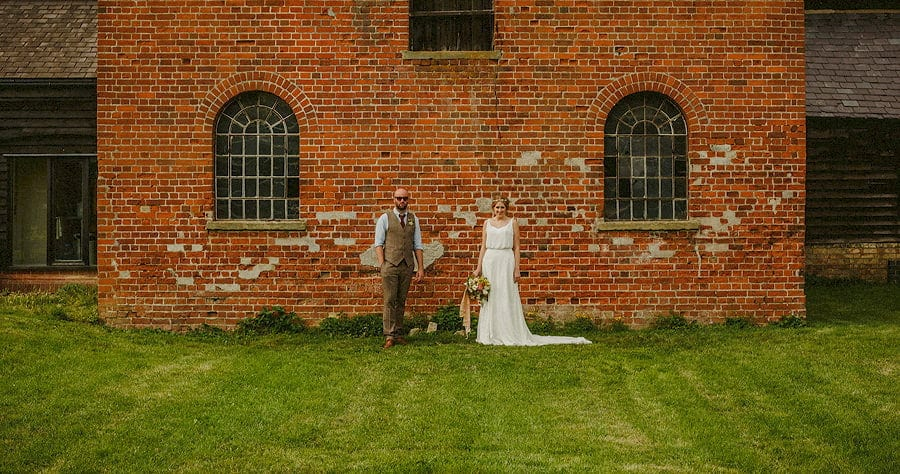 The bride and groom stand next to a large wall and pose for a photograph at Childerley Estate