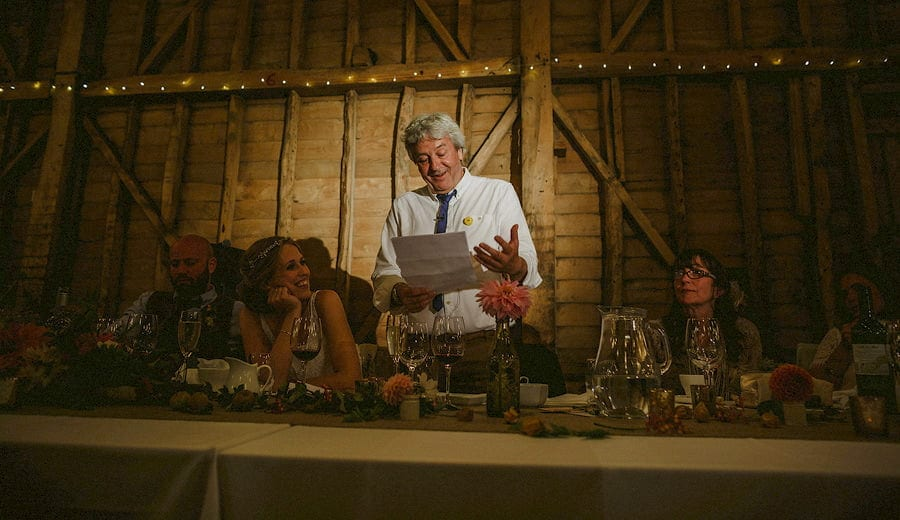 The bride's father delivers his speech in the old barn at Childerley