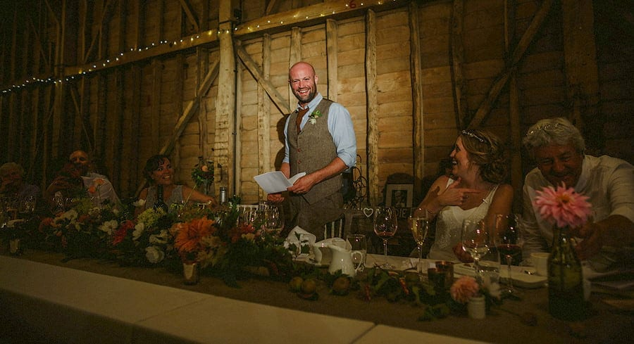 The groom smiles as he stands in front of wedding guests and delivers his speech in the old barn at Childerley