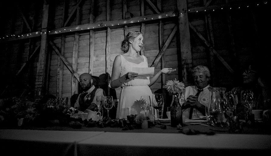 The bride stands in front of wedding guests and delivers her speech in the old barn