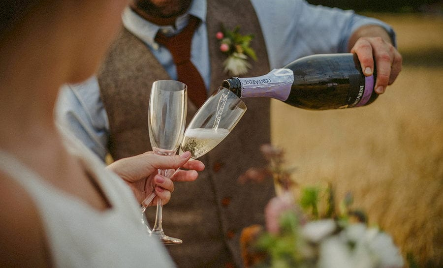 The groom pours champagne into glass flutes held by the bride