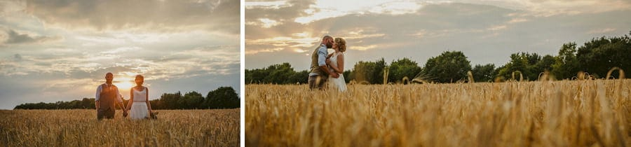 The bride and groom pose for a photograph in a wheat field next to the old barn