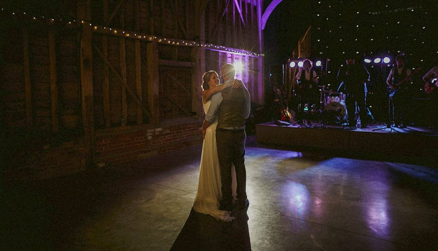 The bride and groom embrace each other on the dancefloor in the old barn at Childerley