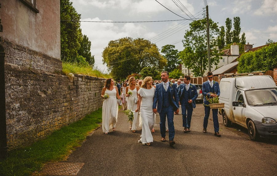 The bride and groom leave the church and walk down the street
