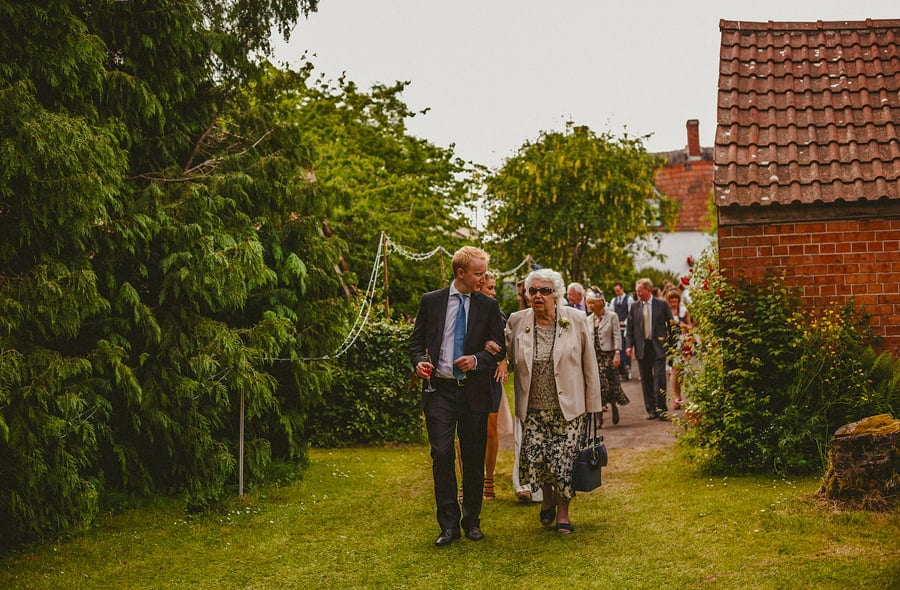 The family of the bride and groom make their way into the back garden