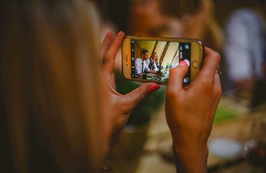 A lady takes a photograph on her mobile phone